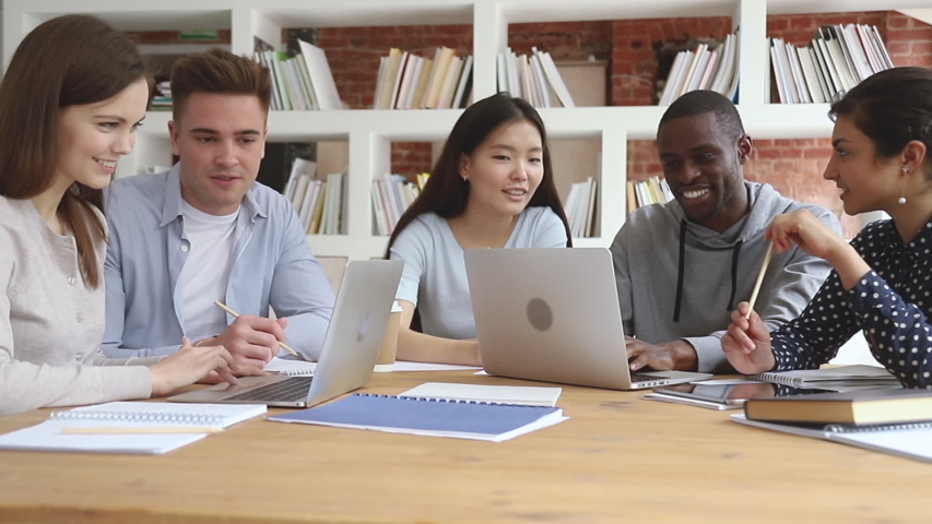 Happy focused diverse students sitting at table, working in groups on computers. Multiracial college friends doing research job homework together in library, preparing for exams, discussing material. Royalty-Free Stock Footage #1042308988