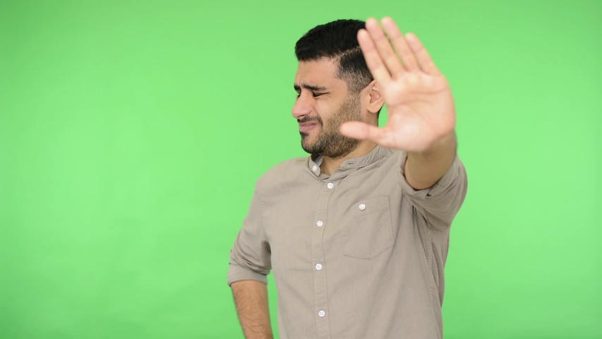Dissatisfied brunette man with bristle in shirt showing stop sign with outstretched hand and saying no, don't show me this, deny reject concept. indoor studio shot, green background, chroma key | Shutterstock HD Video #1042314718