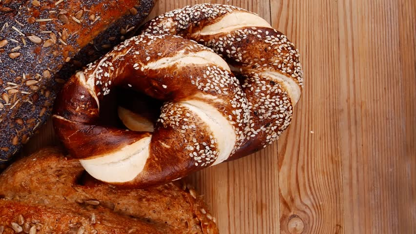 Hot rural french round rye bread and baguette topped with sunflower seeds and sweet bagels on wooden tables 1920x1080 intro motion slow hidef hd | Shutterstock HD Video #10423352