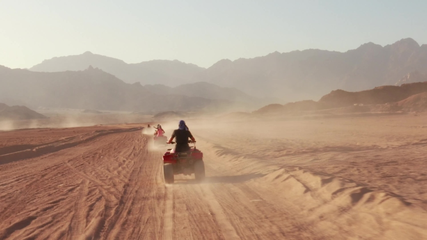Quad bike ride through the desert near Sharm el Sheikh, Egypt.Adventures of desert off-road on ATV.Sand and Sand Borkhan. Rock and sunset. Quad Cycle Travel. Excursion with people. | Shutterstock HD Video #1042337860
