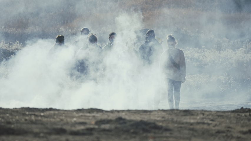 Group of young people in gas mask going through the toxic smoke in a desolate and burned out forest landscape. | Shutterstock HD Video #1042340431