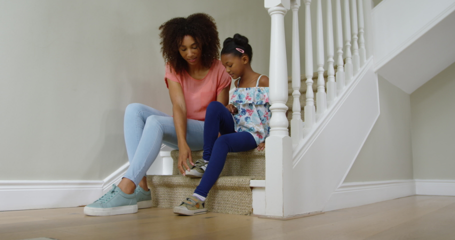 African American woman and her young daughter sitting on the stairs in the hallway. Social distancing and self isolation in quarantine lockdown for Coronavirus Covid19 | Shutterstock HD Video #1042345057