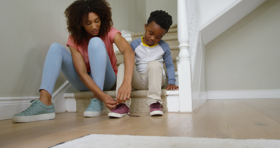Front view of an african american mother and her young son sitting on the stairs in the hallway at home. Social distancing and self isolation in quarantine lockdown for Coronavirus Covid19 | Shutterstock HD Video #1042345066