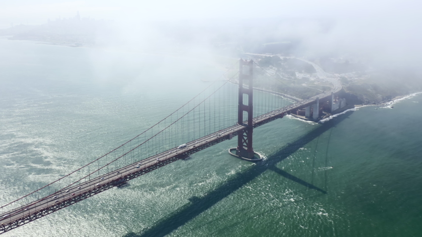 Drone flies high in the sky above floating clouds. Below, overlooks an impressive view of the picturesque Golden Gate Bridge, stretching across the Golden Gate Strait in San Francisco. Aerial. 4K