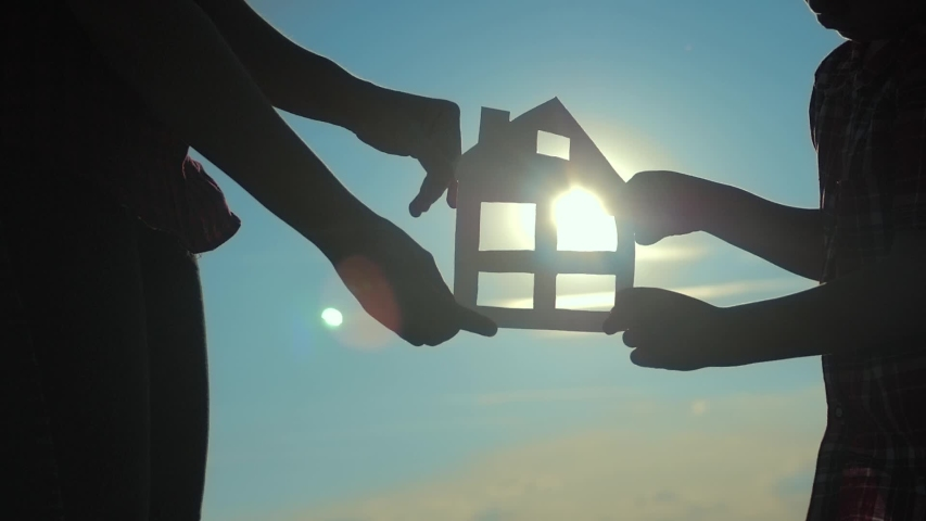Happy family construction house teamwork concept. Mom and son holding home a paper house in his hands at sunset silhouette sunlight. life symbol ecology video. boy and lifestyle girl hold paper home