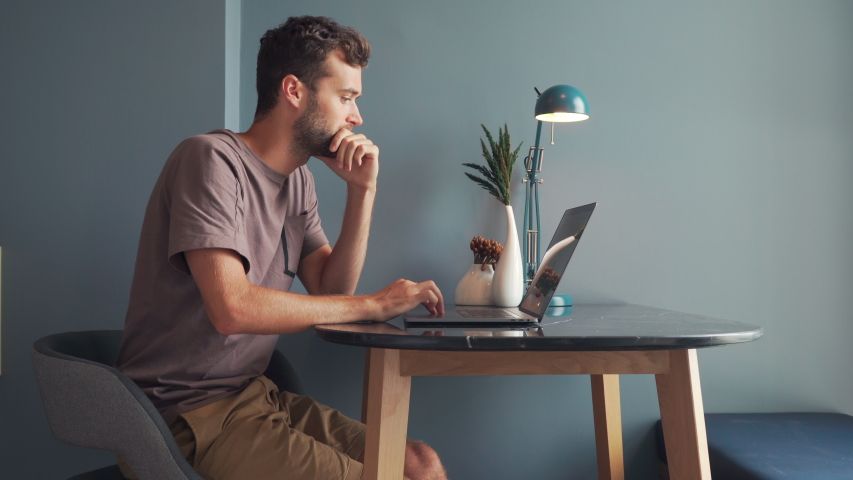 Young Man Freelancer Using Laptop, Typing, Scrolling, Surfing Web, Looking at the Screen. Professional Creative Millennial Sitting at His Desk in Home Office Studio Working 4K. Student Studying Online Royalty-Free Stock Footage #1042391749