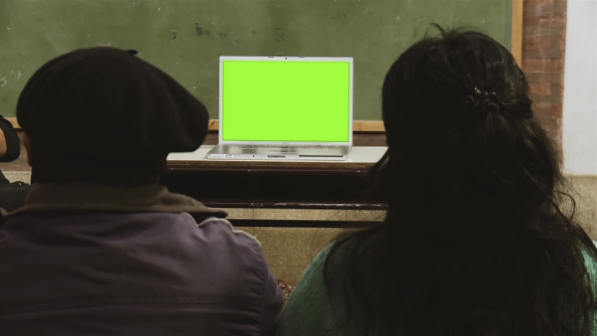 """People Sitting at School and Watching a Laptop with Green Screen. You can Replace Green Screen with the Footage or Picture you Want with """"Keying"""" effect in After Effects (check out tutorials)."""