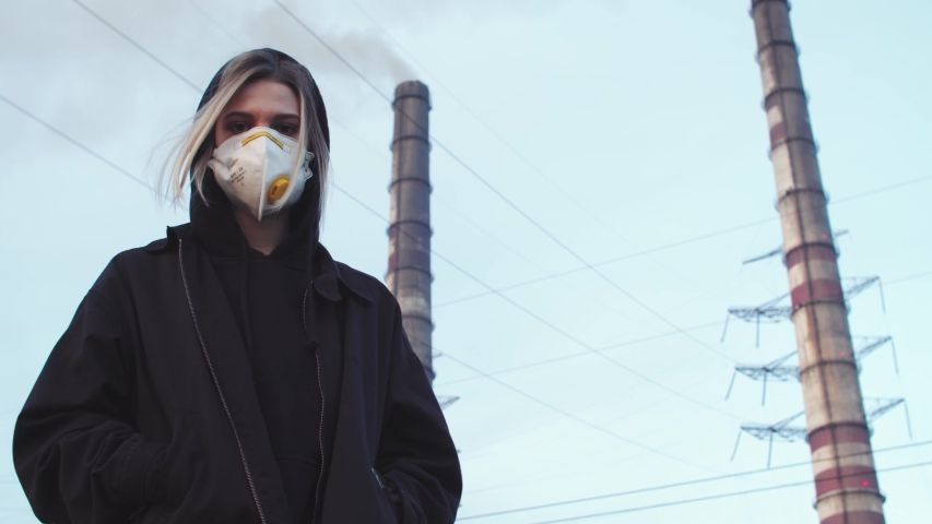 Blonde woman in breathe face protection mask turning and looking at camera with working factory on background. Air pollution. Global political problem. Climate crisis. Activist caring about nature. | Shutterstock HD Video #1042412668