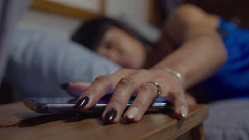 Tired woman in pajamas sleeping in cozy bed, being woken up by alarm clock, reaching out for cellphone on nightstand and snoozing alarm clock on smartphone screen in early morning, unable to wake up. | Shutterstock HD Video #1042419079