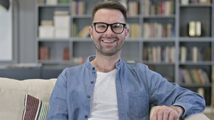 Portrait of Cheerful Young Man Sitting on Sofa and Smiling | Shutterstock HD Video #1042431997