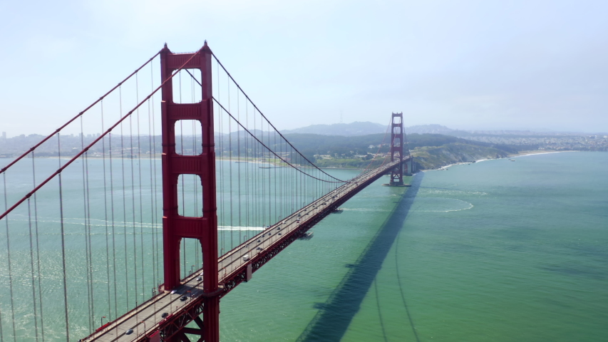 Famous Golden Gate Bridge, the symbol of San Francisco and the entire Pacific coast of the United States. Beautiful red metal construction over the water of the strait. Impressive aerial footage, 4K.