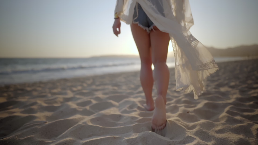 Woman walks along beach barefoot wearing light flowing dress blowing in the wind Royalty-Free Stock Footage #1042455829