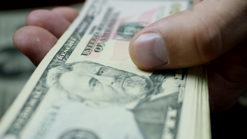 Hands counting US Dollar bills or paying in cash on money background. Concept of investment, success, financial prospects or career advancement | Shutterstock HD Video #1042458229