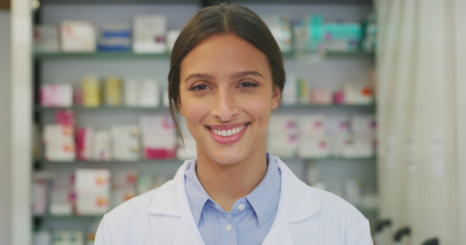 Portrait of an young female pharmacist consultant is smiling in camera in a drug store.
