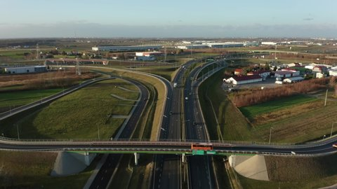 Aerial view of the highway with the movement of cars and vans in the suburbs of Warsaw. Poland. Drone shot on a freeway with bridges and viaducts on a sunny evening.