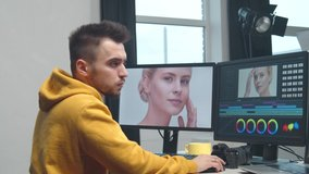 Freelance videographer colorist editing footage using professional software, monitor and montage console.