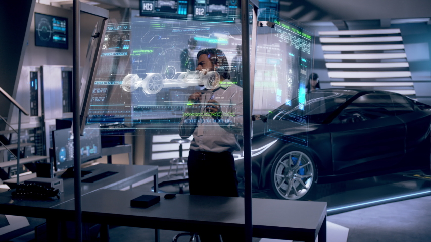 Professional Male Engineer interacts with Black Holographic 3D Concept Car wearing Augmented Reality Glasses inside High-tech Industrial Facility. Car Chassis Prototype. The Future of Hololens Tech