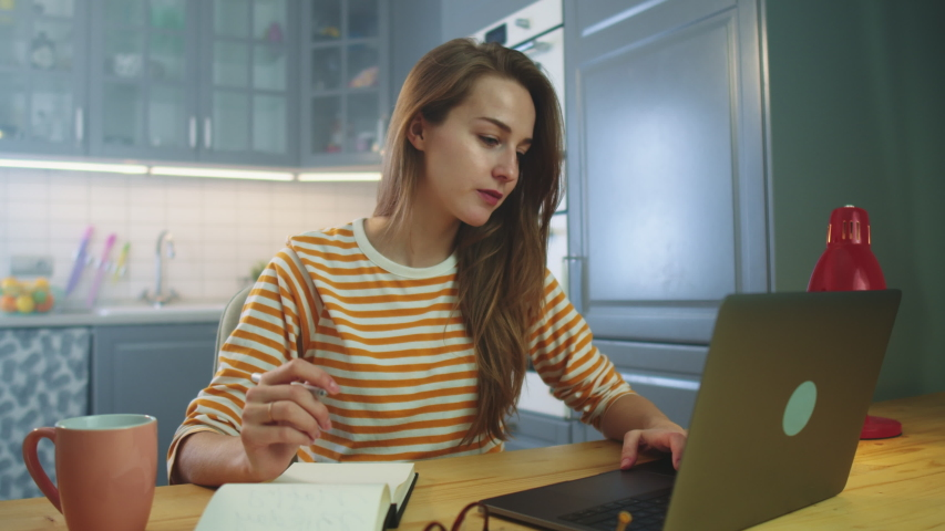 Young cute girl with long hair studying at home using modern laptop, Student girl in casual clothes browsing internet while working from home, Education People Freelancer Self Development Royalty-Free Stock Footage #1042507234