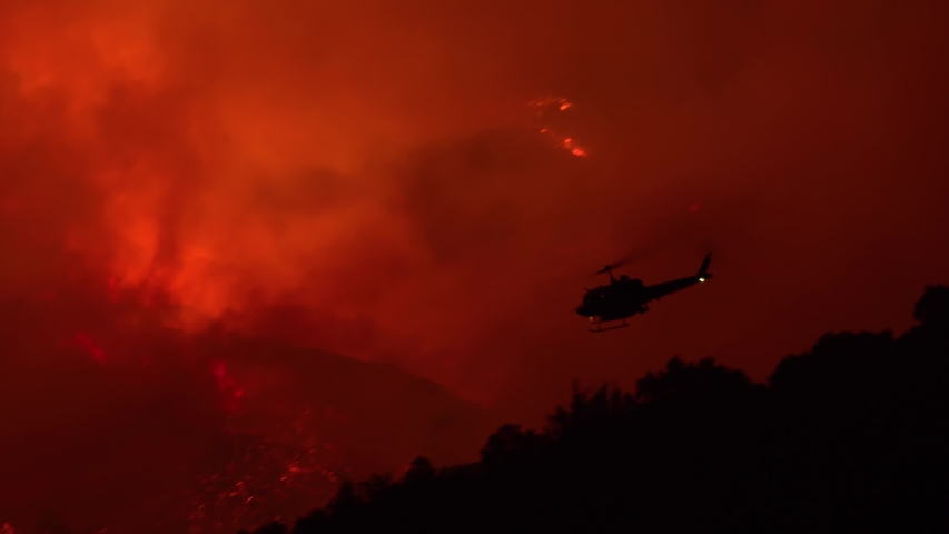 SANTA BARBARA, CALIFORNIA - CIRCA 2010s - a helicopter makes a dramatic water drop at night responding to the Cave Fire near Santa Barbara. | Shutterstock HD Video #1042512364