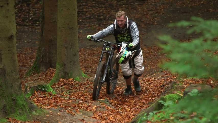 Forest of Dean / United Kingdom (UK) - 03 31 2019: Mountain biker pushes bike up hill
