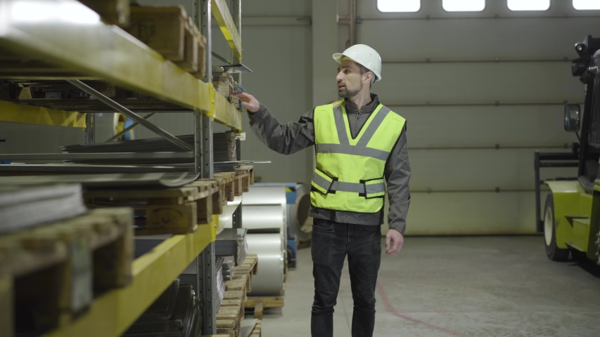 Male Caucasian worker in vest and helmet checking warehouse as his colleague coming up and shaking his hand. Metal plant employees at workplace. Professionals, manufacture. | Shutterstock HD Video #1042522870