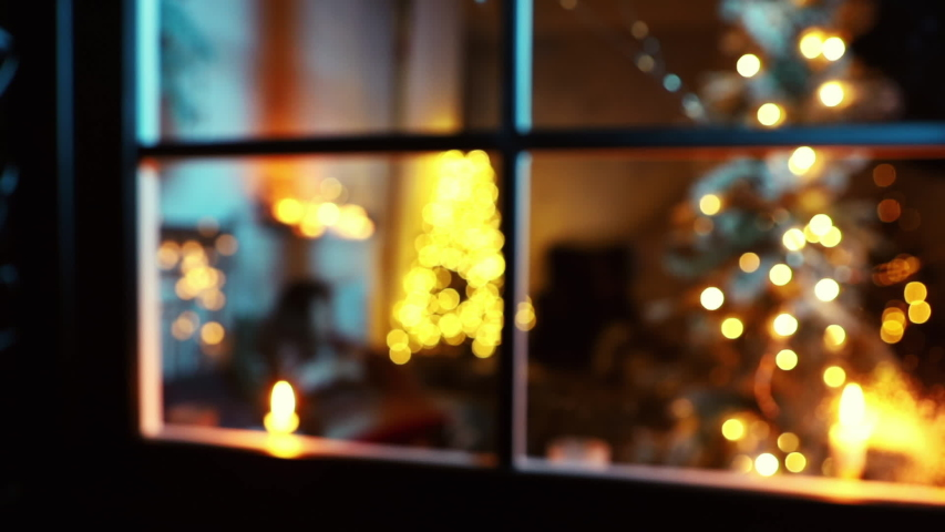 Blurred background of little girl write letter to Santa near christmas tree in bed, christmas and new year eve concept, shoot through window
