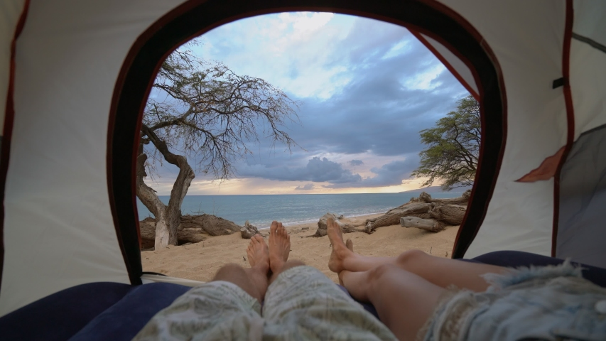 Young couple lying in a camp tent closed up point of view on male and female legs with sea view on stunning beach at sunset  | Shutterstock HD Video #1042525444