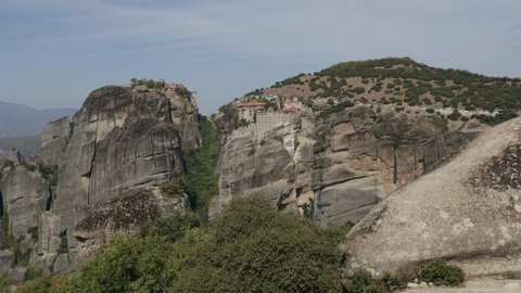 Cars and buses on top of the Meteora rock monastery complex slow pan 4K video