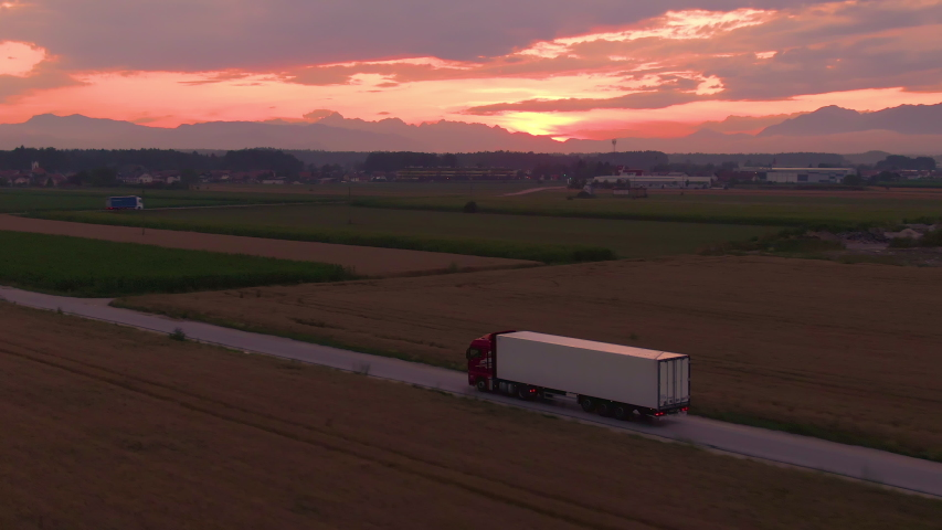 AERIAL: Flying along a cargo truck transporting goods across the picturesque countryside at golden sunrise. Lorry drives goods towards a logistics center in the countryside on a sunny summer evening. Royalty-Free Stock Footage #1042541968