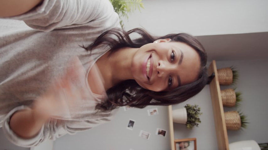 Vertical handheld waist-up shot of vivacious young mixed race woman with genuine toothy smile standing by window at home with outstretched hand and having friendly personal chat on video call
