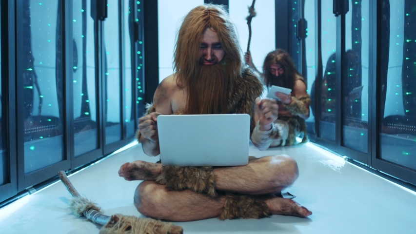 Primeval IT engineer using laptop computer discovering technology at modern database. Happy savage neanderthal dancing with joy having fun staying at data center.