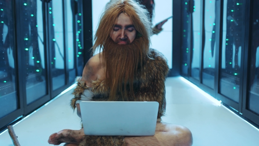 Gloomy prehistoric human in animal fur discovering technology in database server. Ancient IT engineer typing on laptop winning celebrating business success working at data center. Royalty-Free Stock Footage #1042548622