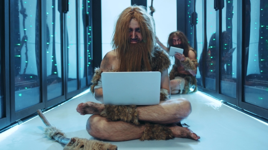 Euphoric caveman celebrating business success using a laptop clenching fists rejoicing while sitting on floor in server cabinet. Prehistoric happy IT specialists working at data center. Royalty-Free Stock Footage #1042548628