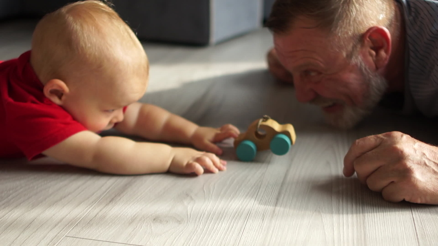 Grandfather playing with little grandson with a toy wooden car, caring granddad and cute preschool grandchild lying on warm floor together, having fun at home, underfloor heating concept close up Royalty-Free Stock Footage #1042553770