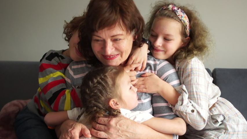 Grandmother posing with grandchildren. Two girls and one boy. Happy children hug their grandmother, portrait of Indoor. Two generations, a large family, a grandmother and grandchildren Royalty-Free Stock Footage #1042556968