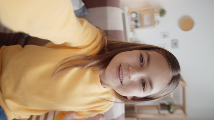 Vertical handheld waist-up shot of cheerful 10-year-old Caucasian girl sitting on couch at home, holding smartphone in outstretched hand, looking at camera and having lively conversation on video call | Shutterstock HD Video #1042557637