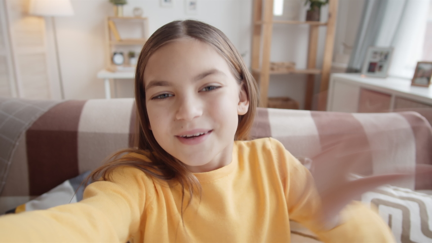 Chest-up handheld shot of happy 11-year-old Caucasian girl sitting on couch at home, holding invisible smartphone in outstretched hand, looking at camera and chatting cheerfully on video call