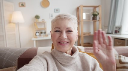Chest-up shot of 50-something Caucasian lady with cropped grey hair sitting on couch at home, holding invisible smartphone in outstretched hand, waving and chatting enthusiastically on video call