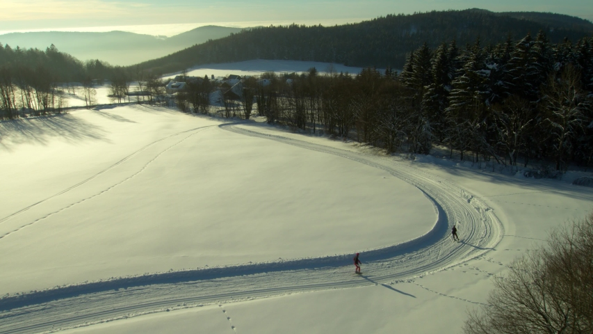 Aerial view in backlit, cross-country downhill skiing on a cross-country trail in a snow-covered landscape in central europe