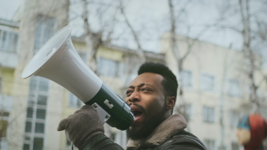 African american man hold megaphone in hand. Shouting out. Political rally. Social activists speack outdoor against. Resistance rebellion. Rebellious requirement activity. Many opposition public mass. | Shutterstock HD Video #1042566298