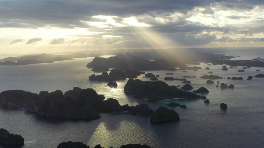 Beams of afternoon sunlight illuminate the scattered rock islands of Raja Ampat, Indonesia. This region is a popular destination for scuba divers and snorkelers due to its high marine biodiversity. | Shutterstock HD Video #1042567711