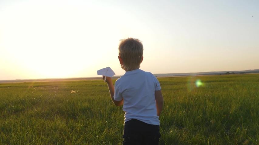Kid with paper plane is run. Happy boy in park. Kid is holding paper plane. Happy boy dream of an airplane. Kid run through park. Airplane pilot boy. Chidhood dream. Happy boy with toy airplane