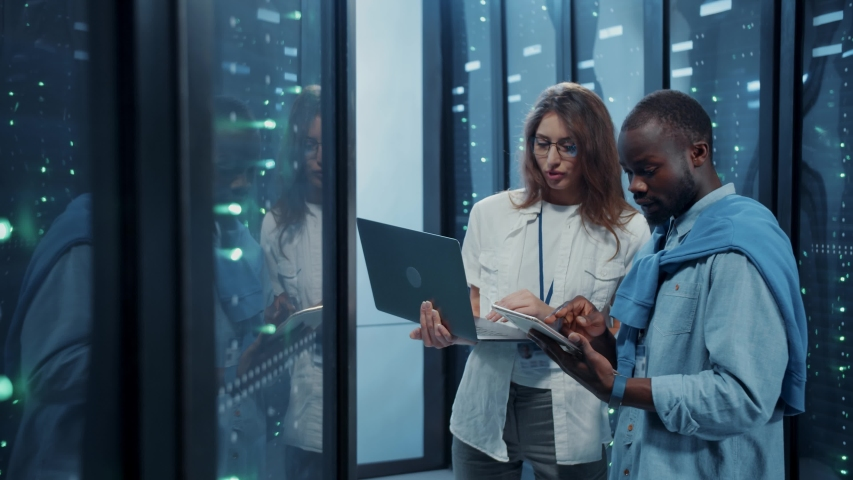 Female IT professional instructing young server technician inside working server cabinet. Male and female server engineers coworking with laptop inspecting data center cyber security. Royalty-Free Stock Footage #1042577083