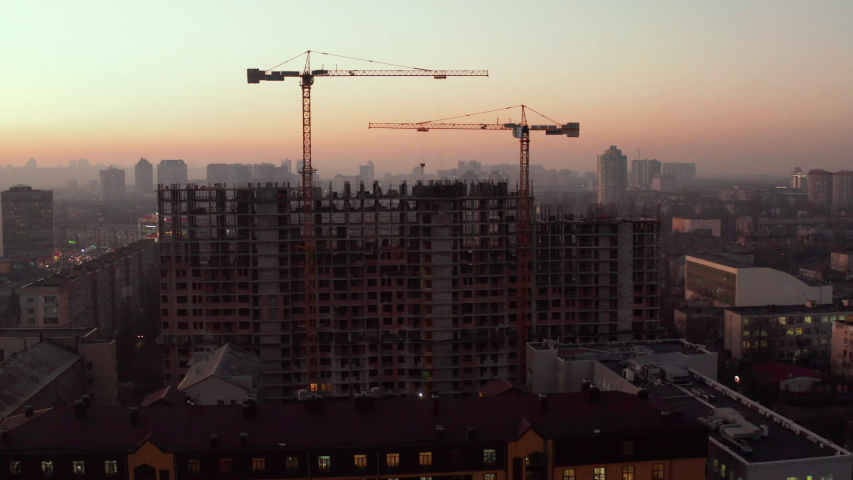 In the Background Working Crane and city. Aerial Shot of the Building in the Process of Construction. Labor working in big construction site | Shutterstock HD Video #1042578082