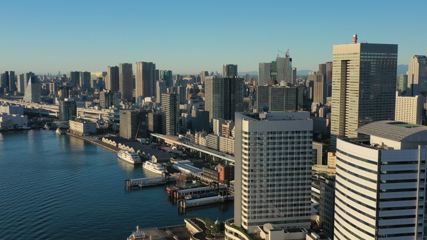 Aerial view of cityscape of Tokyo at sunrise, waters of Tokyo Bay and skyscrapers skyline of modern Japanese capital city, clear blue sky - landscape panorama of Japan from above, Asia | Shutterstock HD Video #1042583728