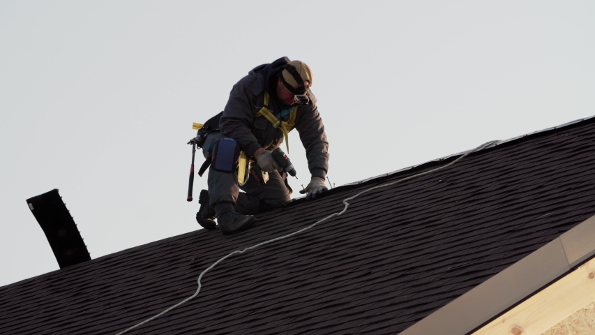 Professional tiler in safety harness is making roof ridge with hydraulic hammer. Works at height. Wooden frame house under construction