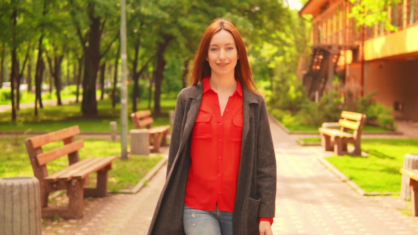 Cheerful redheaded female walking smiling in town surrounded green trees and grass caucasian young woman with long red hair walks on the street | Shutterstock HD Video #1042600273