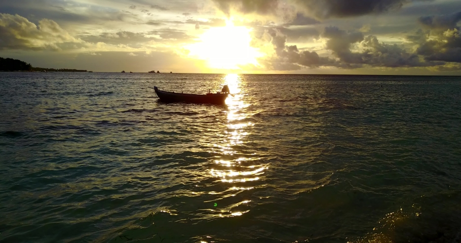 Isolated boat docked in ocean, sunset in Caribbean with yellow sky | Shutterstock HD Video #1042607287