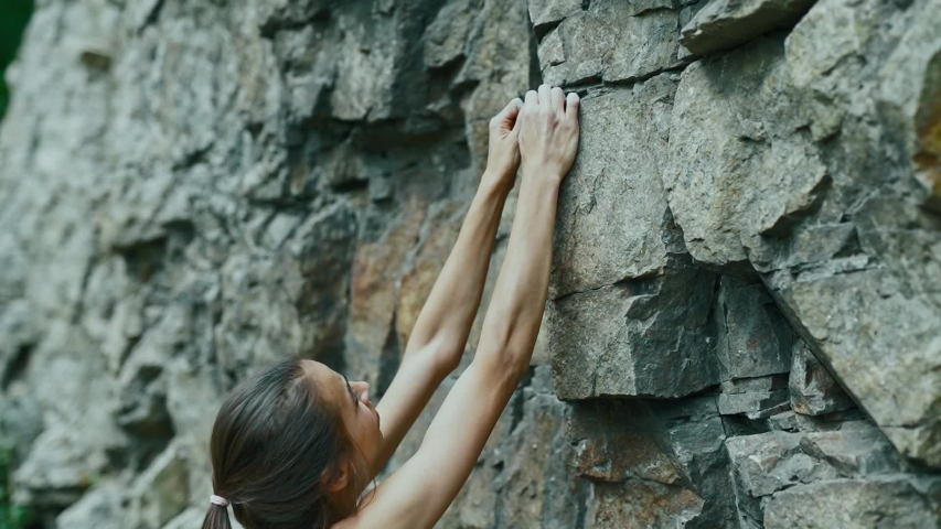 Young slim muscular woman rockclimber climbing on tough sport route, searching, reaching and gripping hold. climber makes a hard move. outdoors rock climbing and active lifestyle, slow motion climbing | Shutterstock HD Video #1042609942