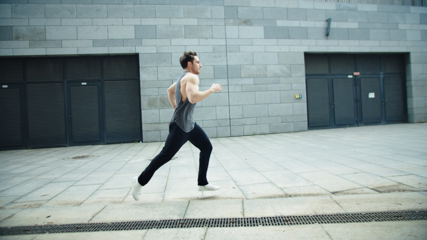Fitness man running on urban street in slow motion. Male runner jogging outdoor. Side view of athlete man training run on city street. Sport man running exercise | Shutterstock HD Video #1042612585
